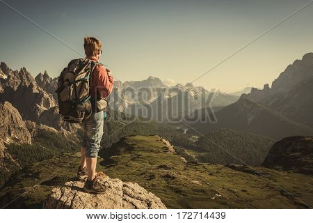 woman traveler with backpack hiking in Tre Cime Park.Italy