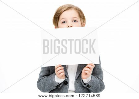 Little boy hiding his face behing blank card on white