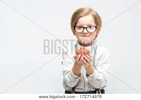 Stylish little boy in eyeglasses holding cupcake and looking at camera