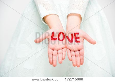 Close-up partial view of word love written on palms of child girl