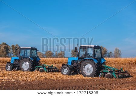 Two Big Blue Tractor Plowing A Field And Remove The Remains Of Previously Mown Corn. The Work Of Agr