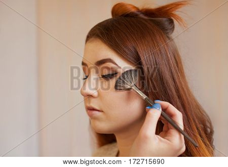 Makeup Artist Applied With A Brush Blush On The Girl's Face, Concludes The Daily Make-up In A Beauty