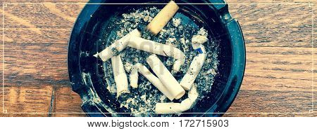 Close up of ash tray with pile of cigarettes and vintage cover look with white thin border