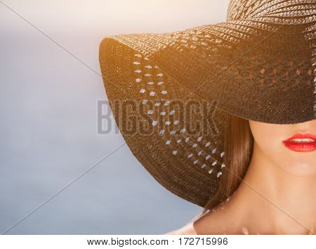 Attractive Girl In A Black Hat Worn On The Head, On The Beach. Close Up Of The Face Can Be Seen.