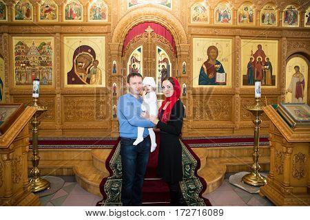 ALMATY KAZAKHSTAN - DECEMBER 17: Christening ceremony on December 17 2013 in Almaty Kazakhstan. Family celebrating baptism in Orthodox Church - Monastery of St. Matrona