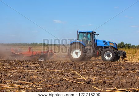 Big Tractor Plows The Field And Removes The Remains Of Previously Mown Sunflower. Work Agricultural