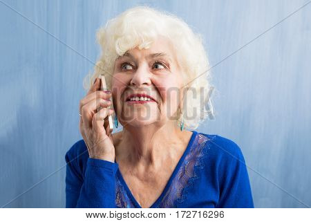 Happy grandma talking on smartphone and smiling