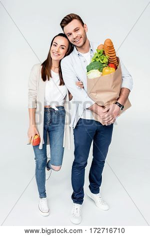 Happy Young Couple Standing Together With Grocery Bag And Smiling At Camera