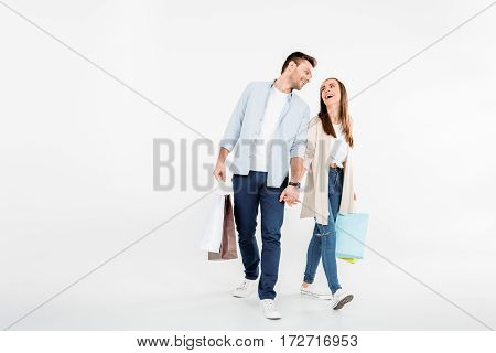 Happy young couple walking with shopping bags and looking at each other