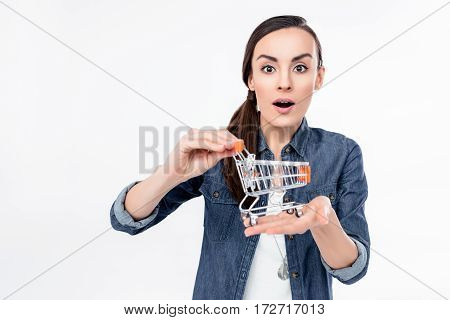 Shocked young woman holding shopping cart model on white