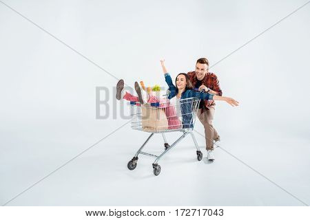 Happy young man pushing shopping cart with excited woman and grocery bag on white