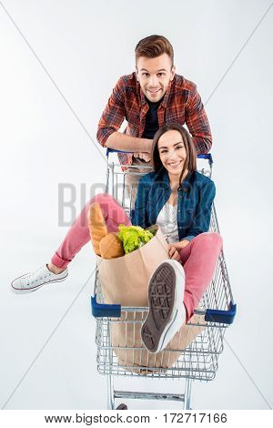 Happy Young Couple With Shopping Cart And Grocery Bag Smiling At Camera