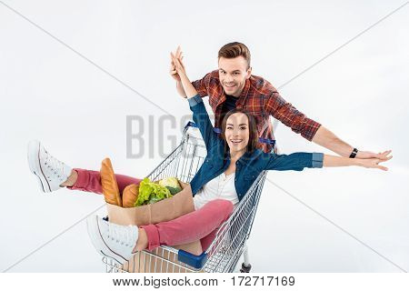 Smiling Young Man Pushing Shopping Cart With Excited Young Woman And Grocery Bag
