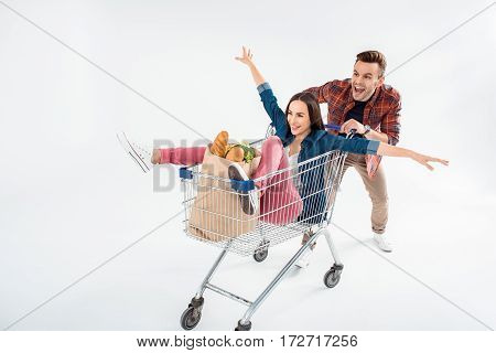 Happy Young Man Pushing Shopping Cart With Excited Young Woman And Grocery Bag