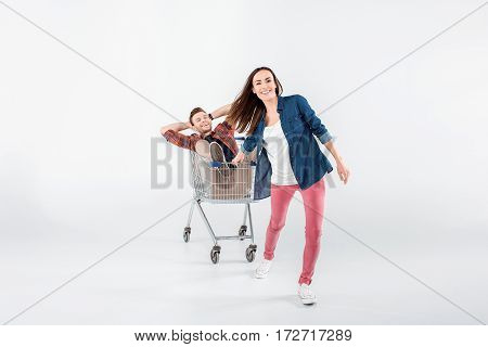 Smiling Young Woman Carrying Happy Man In Shopping Cart On White