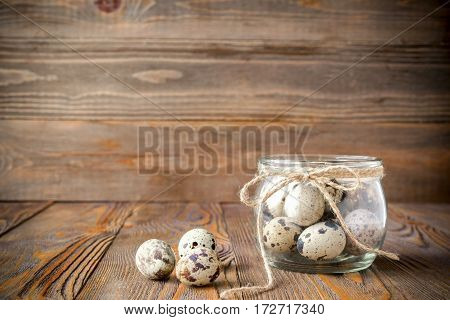Fresh quail eggs in a glass jardecorated with a linen rope kitchen wooden table. Dark background close-up. Front view horizontal frame. . Copy space