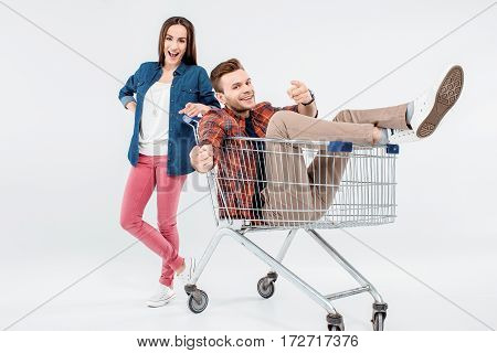 Smiling Young Woman Leaning On Shopping Cart With Happy Young Man