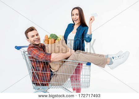 Happy Man Sitting In Shopping Cart With Grocery Bag And Smiling Woman Showing Blank Card