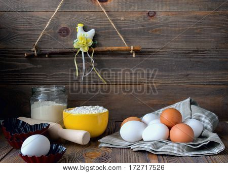 Fresh chicken eggs kitchen wooden table for making a festive Easter cake dark background. Front viewhorizontal frame.Copy space
