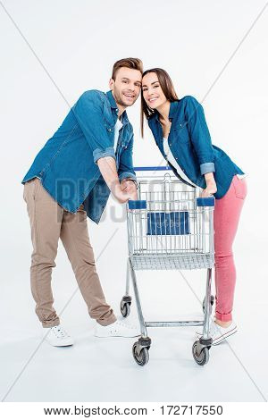 Happy Young Couple With Empty Shopping Cart Smiling At Camera