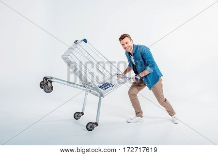 Excited young man having fun with shopping trolley on white