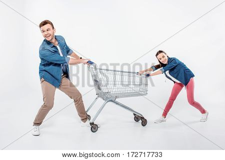 smiling couple pulling empty shopping cart and looking away on white