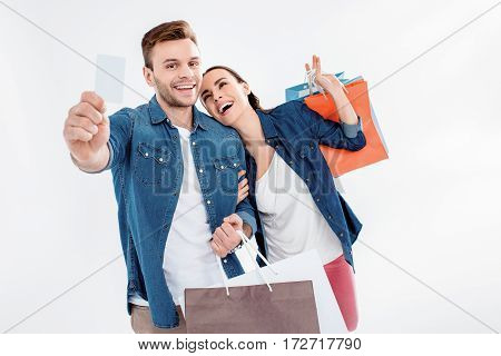 portrait of couple holding shopping bags and credit card on white