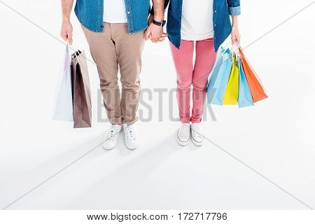 partial high angle view of couple holding shopping bags in hands on white
