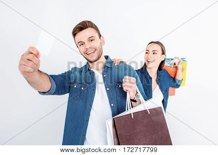 portrait of smiling couple holding shopping bags and credit card on white