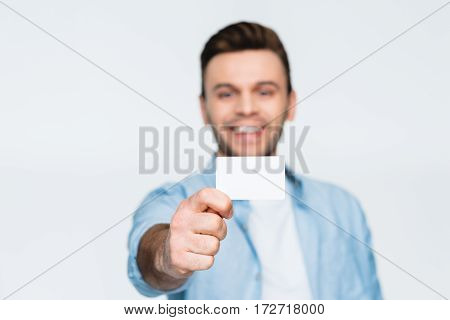 portrait of smiling man showing credit card on white focus on foreground