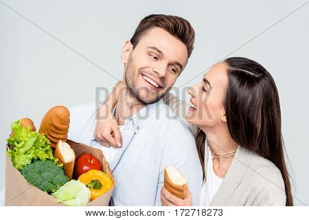 portrait of happy man and woman with grocery bag looking at each other on white