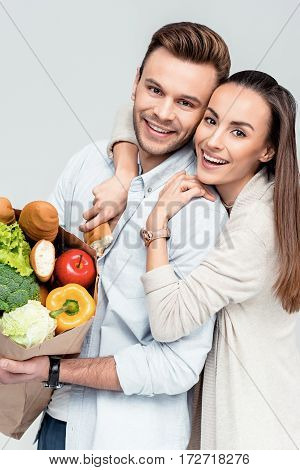 portrait of happy woman hugging man with grocery bag and looking to camera