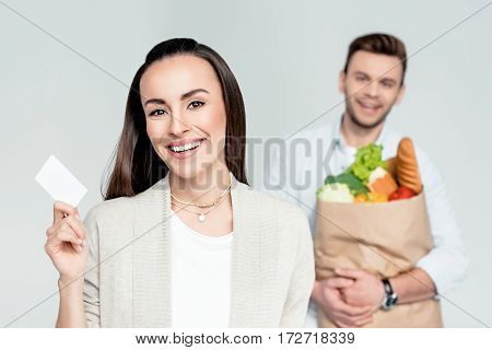 smiling woman pointing to credit card in hand with man behind