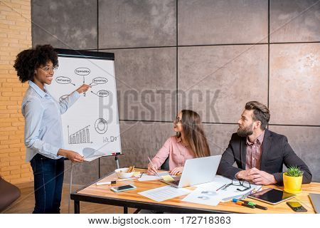 Multi ethnic coworkers having discussion near the whiteboard with charts during the meeting at the workplace