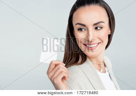 portrait of smiling woman looking at credit card in hand