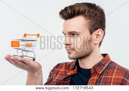 portrait of smiling man looking at shopping cart model on palm on white