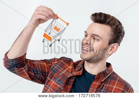 portrait of smiling man looking at shopping cart model on white