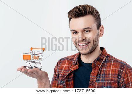 portrait of smiling man holding shopping cart model on palm on white