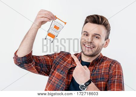 portrait of smiling man pointing at shopping cart model and looking to camera