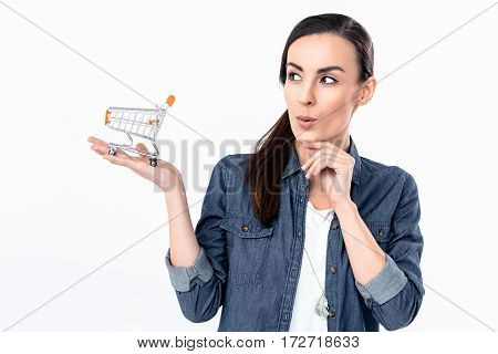 portrait of cunning woman holding shopping cart model on palm