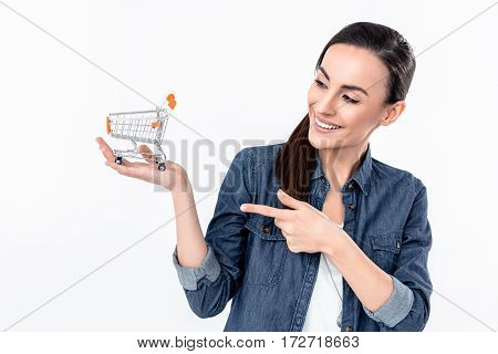 portrait of smiling woman pointing at small shopping cart model on palm