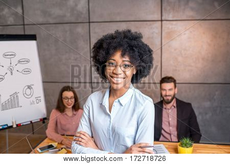 Portrait of a beautiful african businesswoman with coworkers on the background at the office