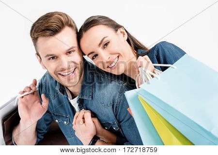 Portrait Of Smiling Couple Holding Shopping Bags And Looking To Camera On White