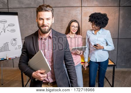 Portrait of a handsome businessman holding laptop at the modern office with coworkers and white board on the background