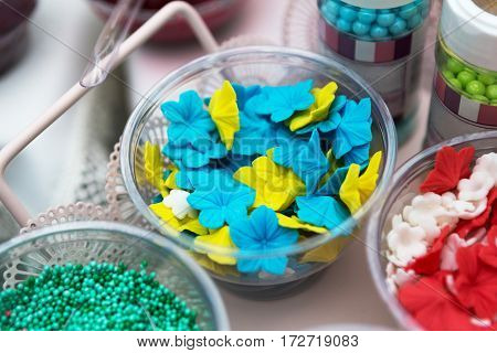 Ice cream treats and toppings sale. Rainbow sprinkles, flowers, non pareil and glitter cupcake decorations, bright yellow and blue. Closeup in plastic plates with spoons. Confectionery store