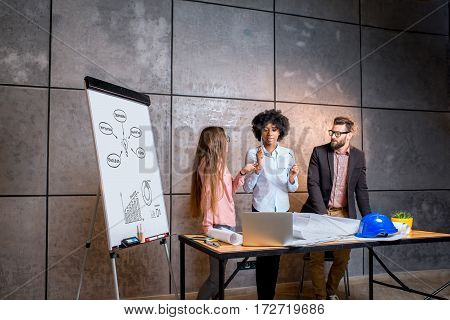 Multi ethnic group of architects or designers working together on the architectural plans at the modern office with whiteboard