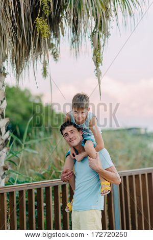 summer day in the park under a palm tree walk a son with his father