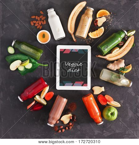 Raw juice cleanse diet. Healthy detox drinks, fruit and vegetable ingredients and tablet with copy space at black background. Smoothie in bottles, top view, flat lay. Internet order online concept