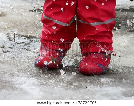 a child in rubber boots running through puddles in the early spring