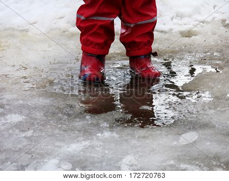 Child wearing red rain boots jumping into a puddle in the early spring
